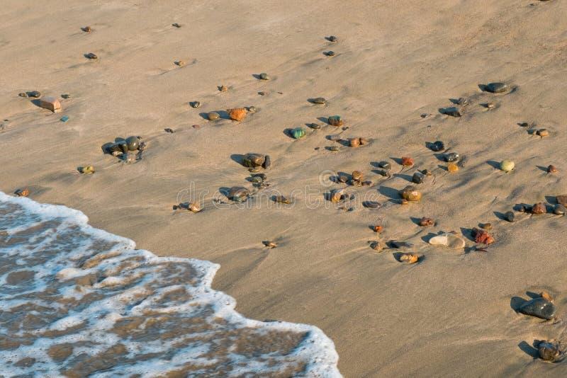 Fal uderzenia wyrzucać na brzeg z kolorowymi otoczaków kamieniami - zbliżenie fotografia stock