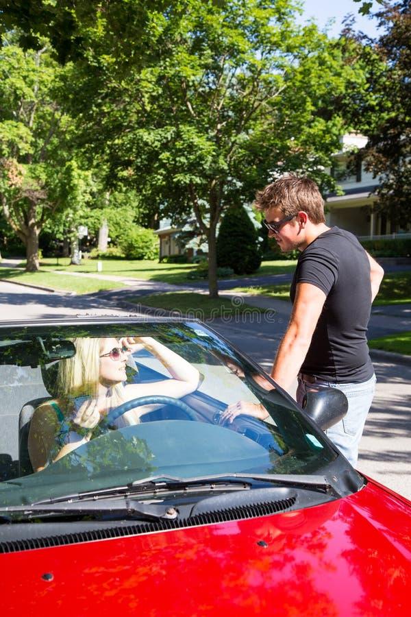 Fala à menina no convertible vermelho fotografia de stock