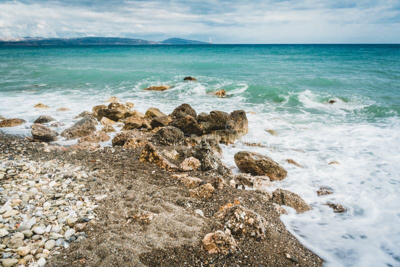 Fala biją przeciw kamieniom na słonecznym dniu w Crete, Grecja Błękitny Denny ocean w tle i kamień wyrzucać na brzeg w obrazy royalty free