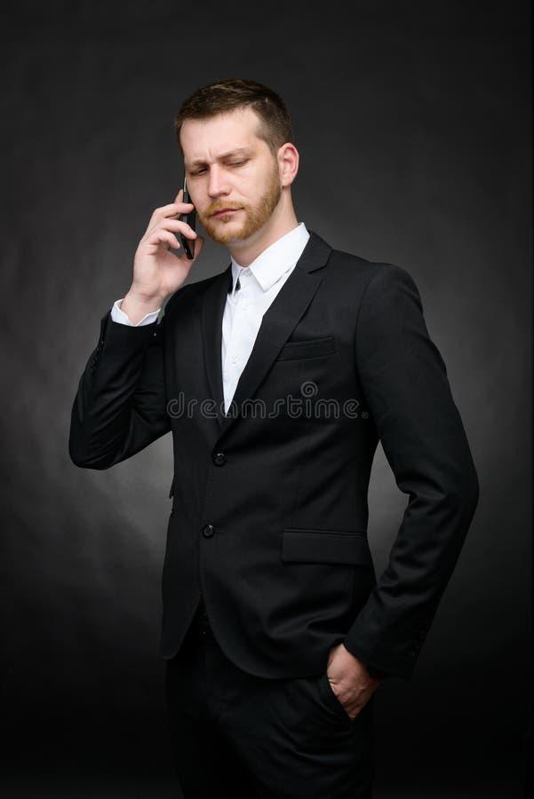 Fala cética do homem de negócios séria no smartphone fotografia de stock