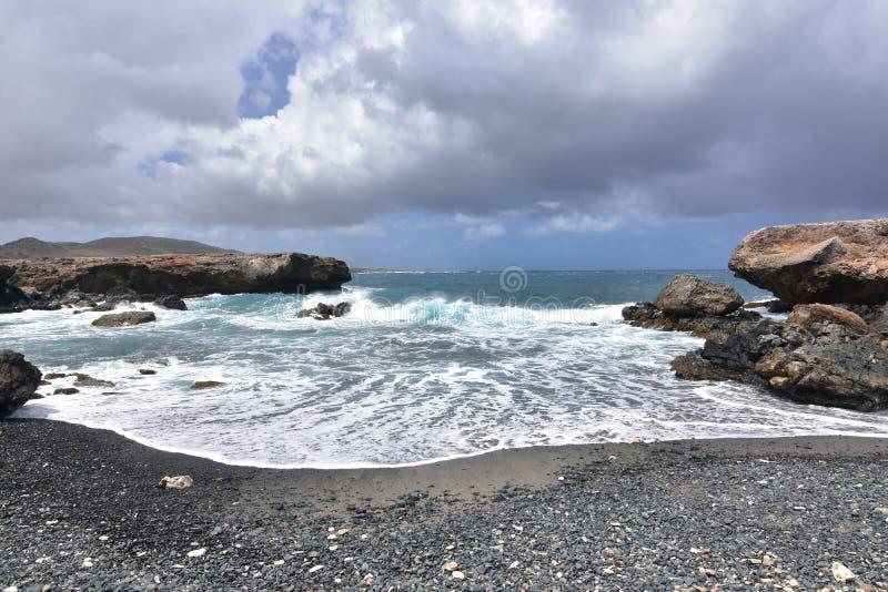 Fala Cofa się na Czarnej otoczak plaży w Aruba fotografia stock