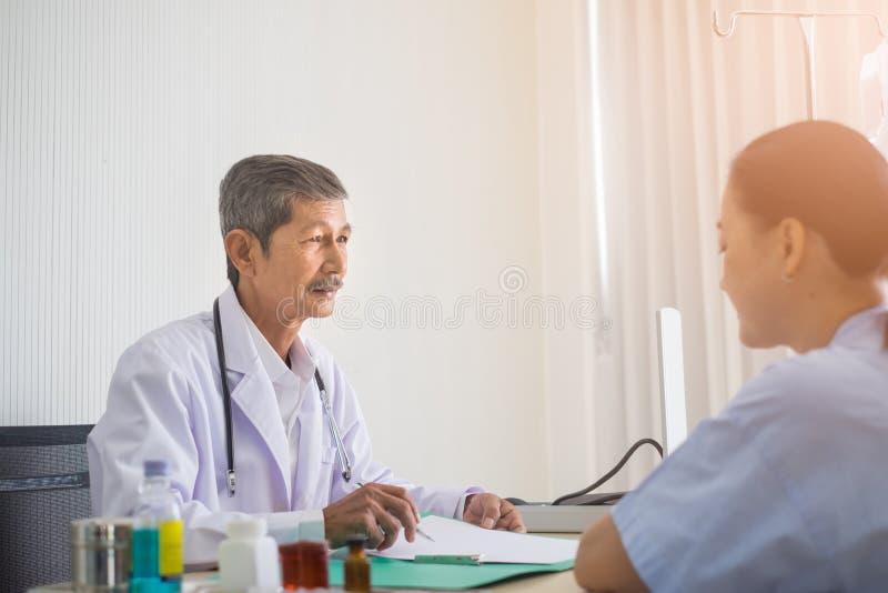 Fala de assento asiática do doutor e do paciente do homem superior na sala de hospital fotografia de stock