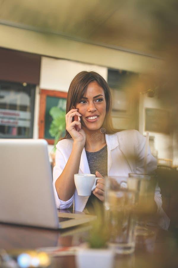 Fala de trabalho de sorriso nova da mulher de negócio no café no telefone fotografia de stock royalty free
