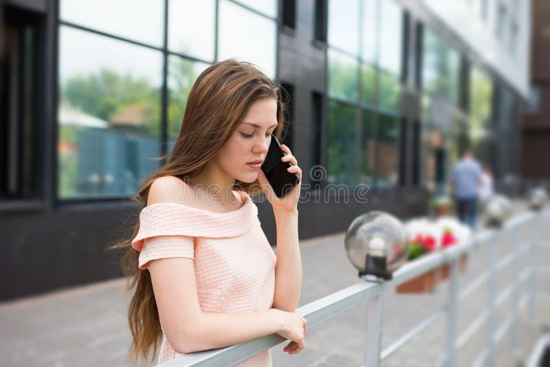 Fala do adolescente séria por um smartphone imagens de stock