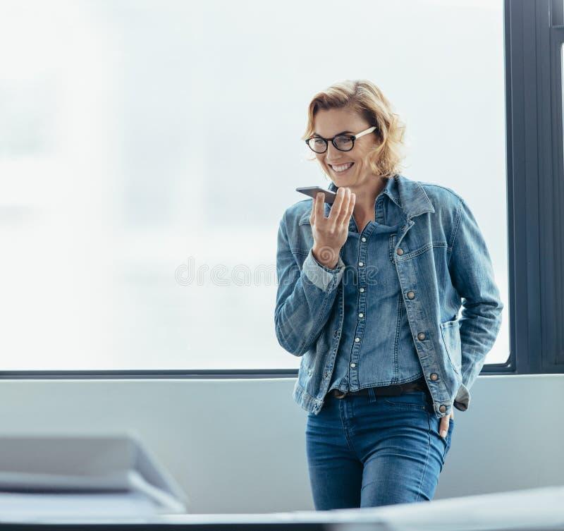 Fala executiva fêmea no telefone de orador fotografia de stock