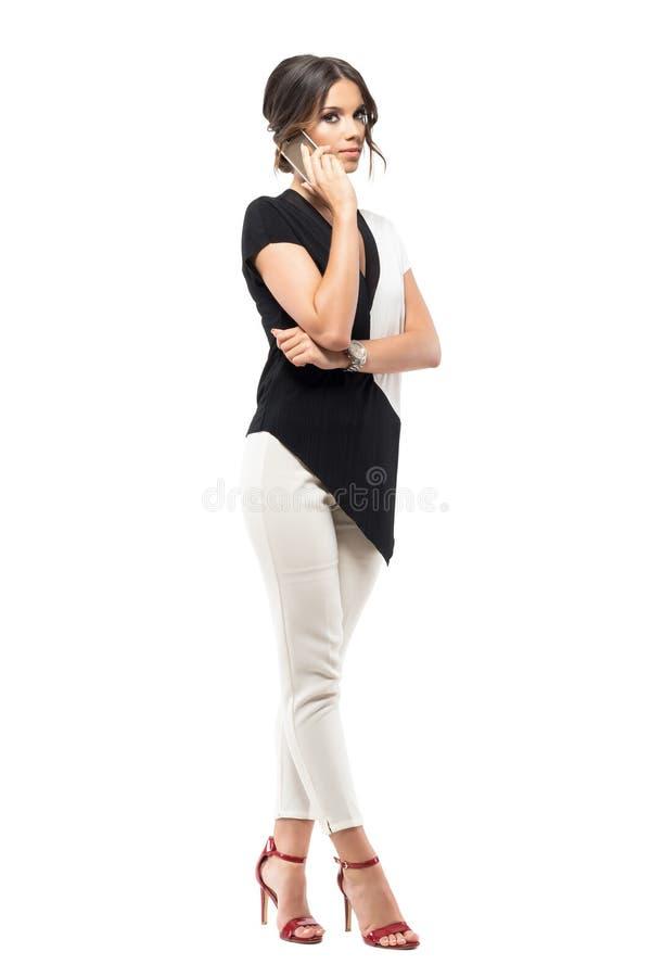 Fala fêmea incorporada bem sucedida segura no telefone que olha a câmera imagens de stock