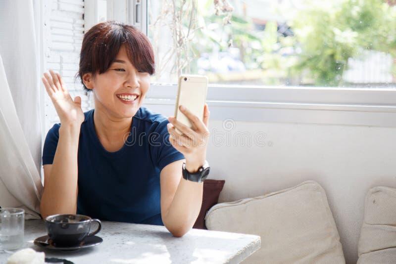 Fala fêmea nova com seu amigo no dispositivo do smartphone cópia foto de stock