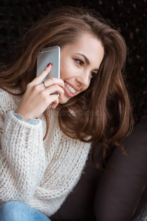 Fala fêmea positiva no telefone celular e no sorriso imagem de stock