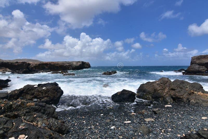 Fala Owija brzeg czerń kamienia plaża w Aruba fotografia stock