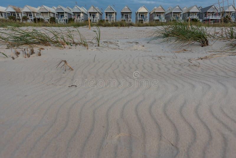 Fala piasek przed Jednolitymi Plażowymi domami obrazy royalty free