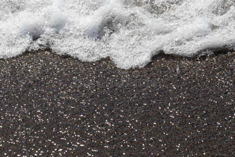 Fala pieni się na piasku Zbliżenie morze macha z biel pianą na piaskowatym brzeg z słońc odbić skutkiem zdjęcia stock