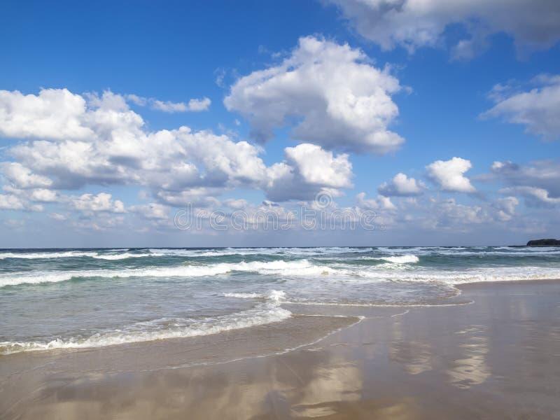 Fala rozprzestrzeniać na piaskowatej Czarnej morze plaży, obłoczni odbicia na piasku, cumulus chmury w niebie zdjęcia royalty free