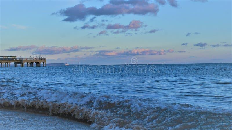 Fala trzaska zmierzchu plaża fotografia stock
