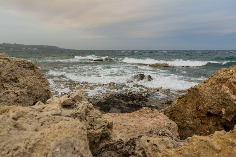 Fala wiatr na morze kamieniu i pluśnięcia wyrzucać na brzeg z dramatycznym niebem zdjęcie stock