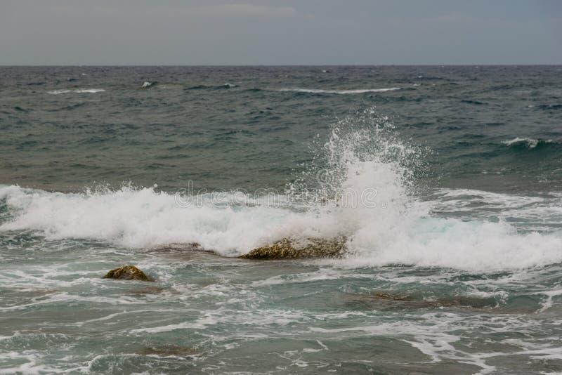 Fala wiatr na morze kamieniu i plu?ni?cia wyrzuca? na brzeg z dramatycznym niebem zdjęcie royalty free