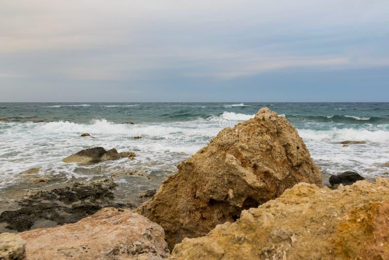 Fala wiatr na morze kamieniu i plu?ni?cia wyrzuca? na brzeg z dramatycznym niebem obraz royalty free