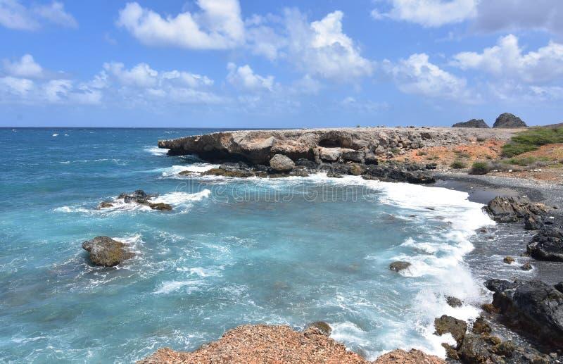 Fala Wiruje Z brzeg Aruba ` s czerni piasek Wyrzucać na brzeg fotografia royalty free