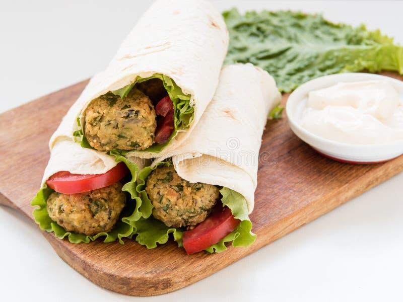 Falafel и свежие овощи свернули в хлебе пита стоковая фотография