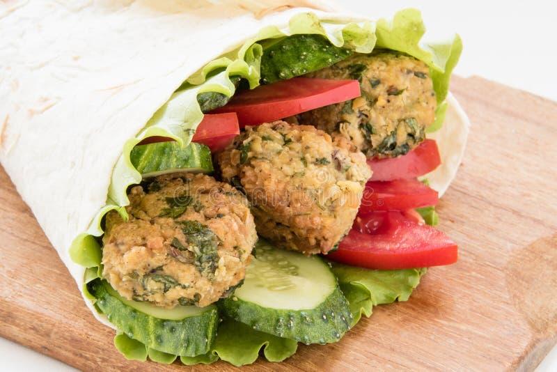 Falafel и свежие овощи свернули в хлебе пита стоковые фото