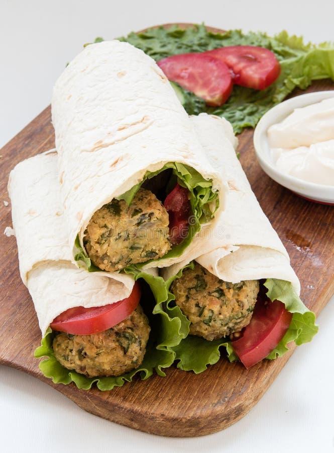Falafel и свежие овощи свернули в хлебе пита стоковое изображение rf