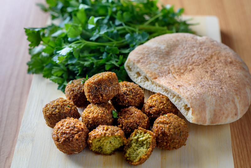 Falafel balls, pita and green fresh parsley on wood rustic background. stock photos