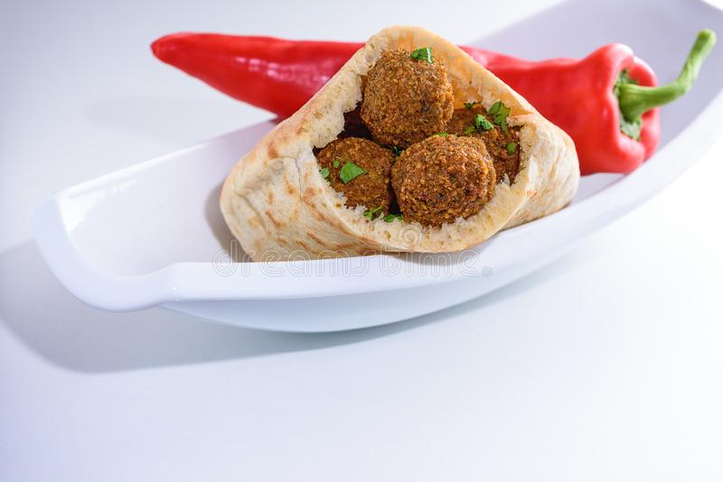 Falafel balls in a pita on a white dish and red sweet pepper background. royalty free stock photo