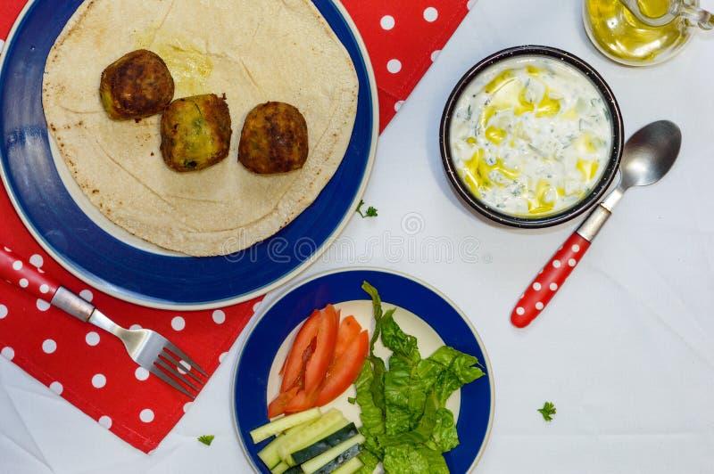 Falafel cozinhado na tabela com vegetais e molho do iogurte fotos de stock