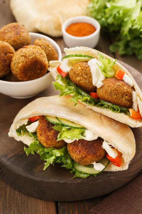 Falafel and fresh vegetables in pita bread with sauce. Falafel and fresh vegetables in pita bread on wooden board stock photo