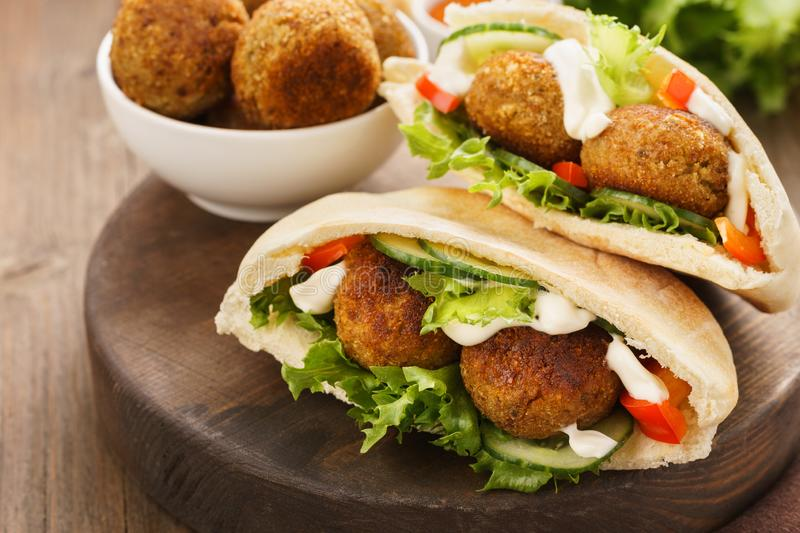 Falafel and fresh vegetables in pita bread with sauce. Falafel and fresh vegetables in pita bread on wooden board stock image