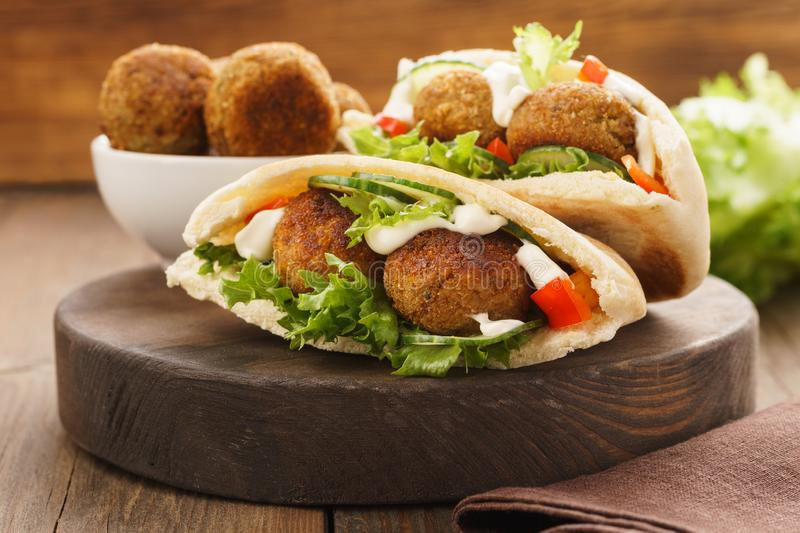Falafel and fresh vegetables in pita bread with sauce. Falafel and fresh vegetables in pita bread on wooden board royalty free stock photo