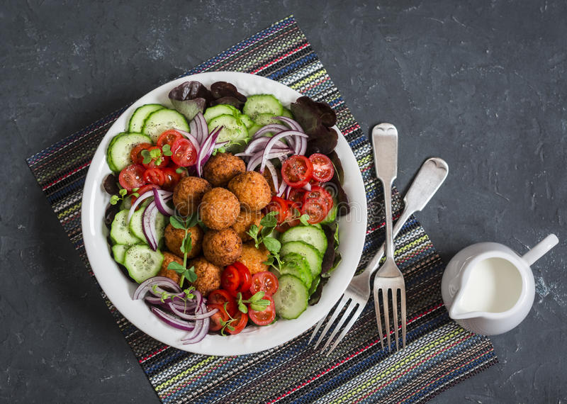 Falafel and fresh vegetables salad on dark background, top view. Vegetarian, diet food. Concept stock image