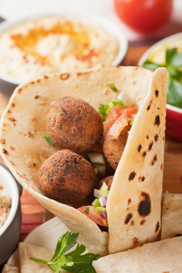 Falafel, frittierte Kichererbsenbälle auf Pittabrot lizenzfreie stockfotos