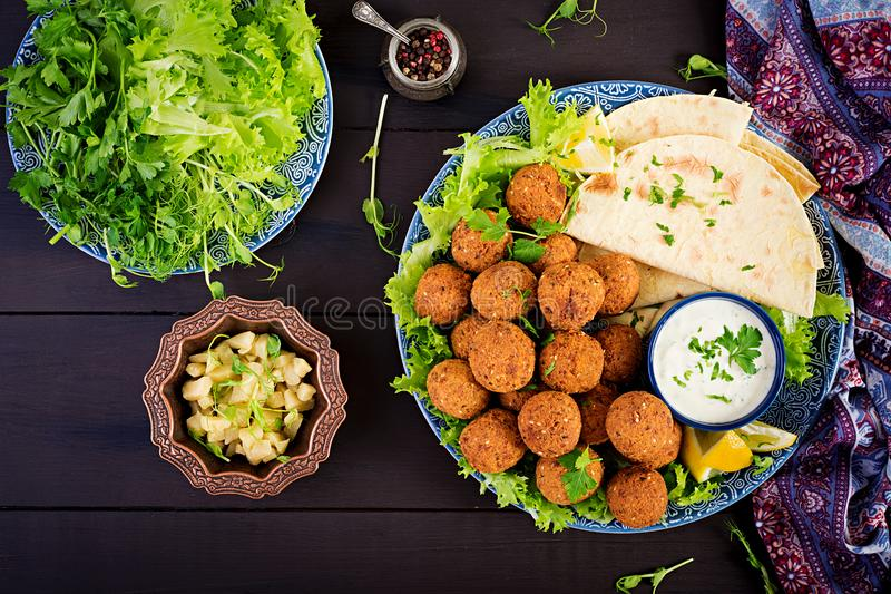Falafel, hummus and pita. Middle eastern or arabic dishes on a dark background. Halal food. Top view. Copy space royalty free stock photography