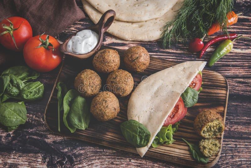 Falafel, nya grönsaker, sås och pitabröd på trätabellen royaltyfria foton