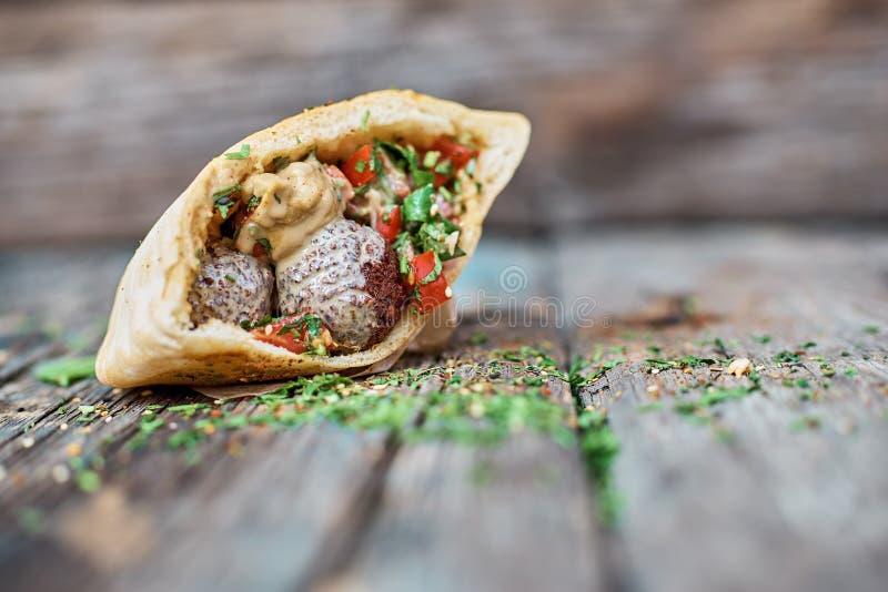 Falafel och nya grönsaker i pitabröd på trätabellen Sund livsstil Selektivt fokusera arkivbild