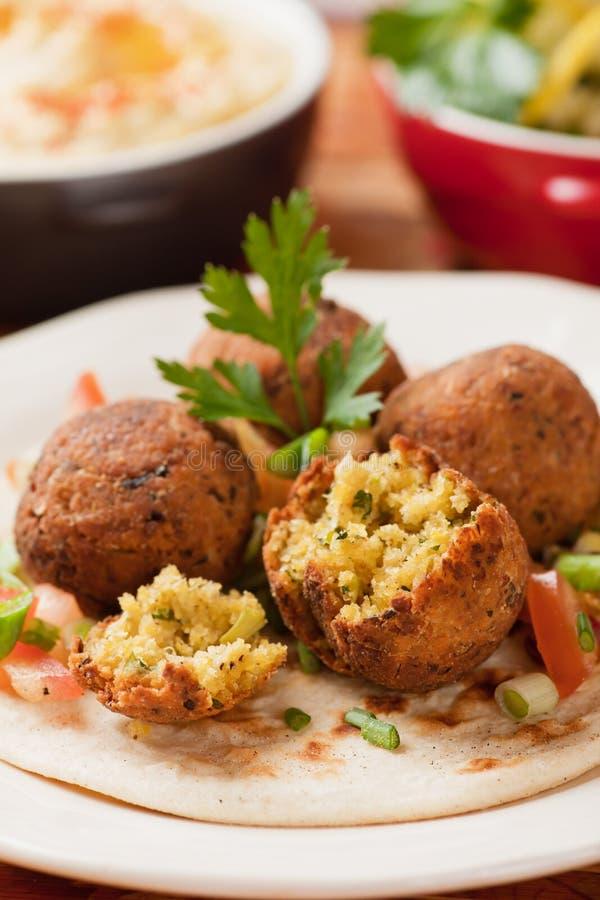 Falafel, palle fritte nel grasso bollente del cece sul pane della pita immagini stock