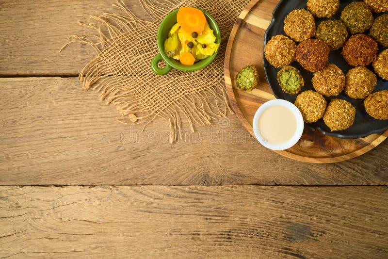 Falafel piłki z tahini kumberlandem na drewnianej desce zdjęcie stock