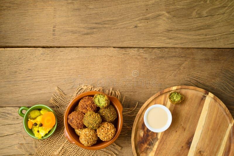 Falafel piłki z tahini kumberlandem na drewnianej desce zdjęcie royalty free