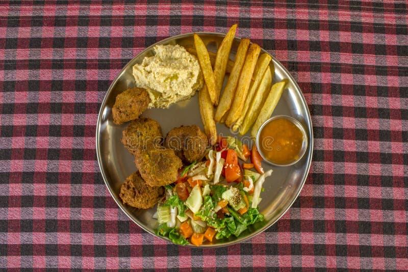 Falafel, pommes de terre, houmous, salade et sauce dans une plaque de métal ronde sur une vue supérieure de nappe noire blanche r images libres de droits