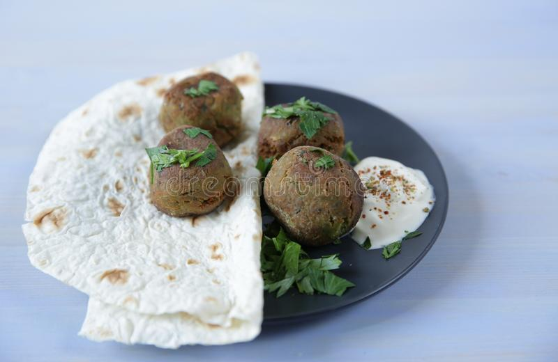 Falafel with tortilla, fresh parsley and souse on the plate on a light color wooden table. Vegan tacos. Vegetarian healthy food. royalty free stock photography