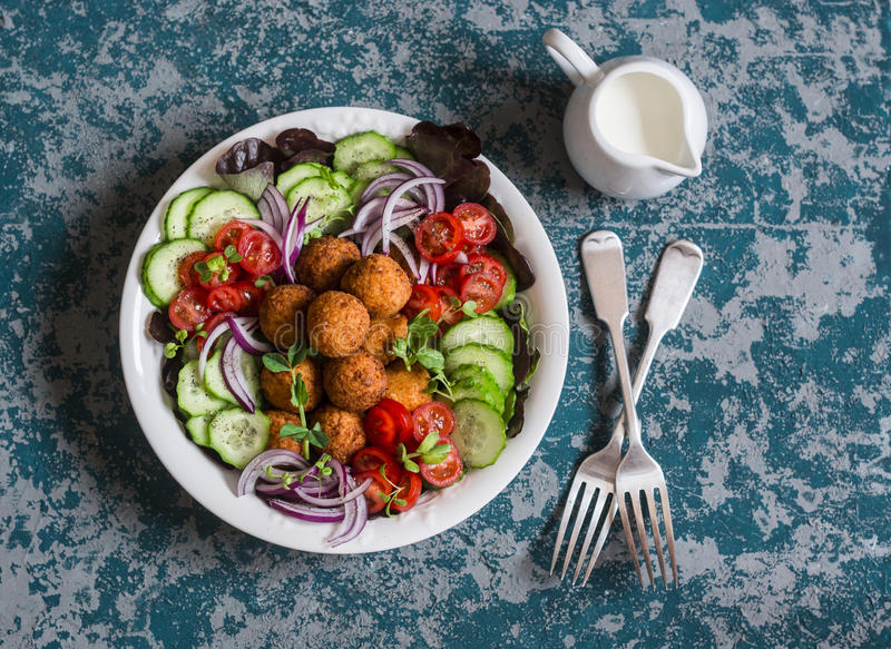 Falafel and vegetables salad. Delicious vegetarian food concept. Buddha bowl on dark background. Top view stock images