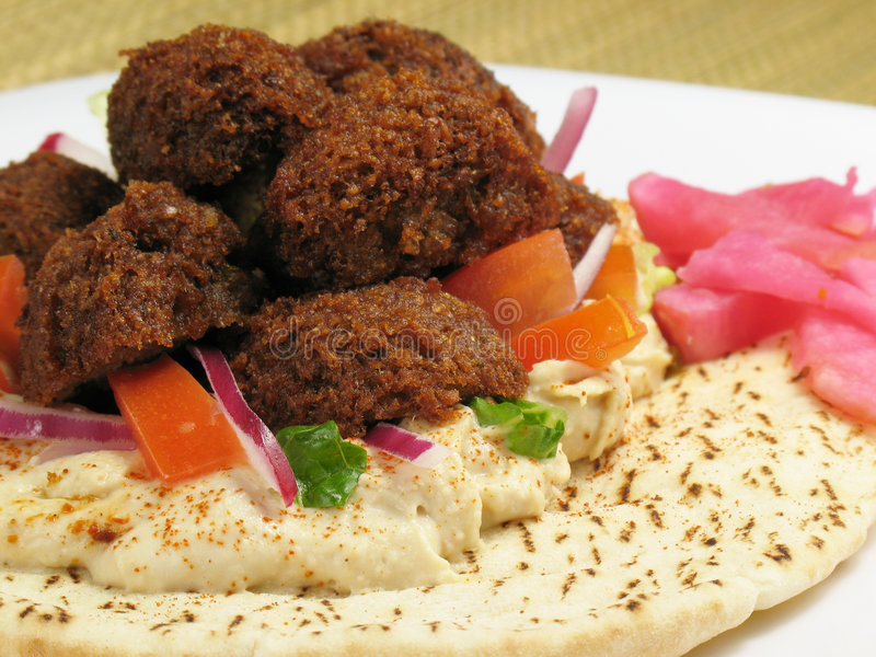 Falafels and Pita Bread. A delicious portion of falafels served on top of a pita bread with hummus, lettuce, tomato, red onions, and a side of turnips pickled in royalty free stock photo