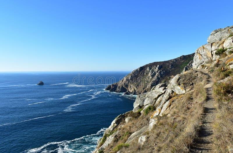 Falaise avec le chemin Roches et mer bleue avec la mousse, jour ensoleillé Finisterre, Galicie, Espagne images stock