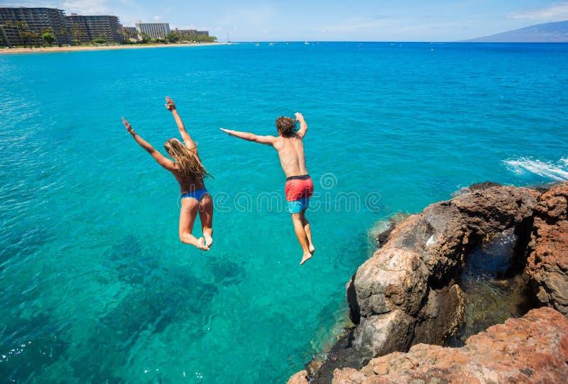 Falaise d'amis sautant dans l'océan photo libre de droits