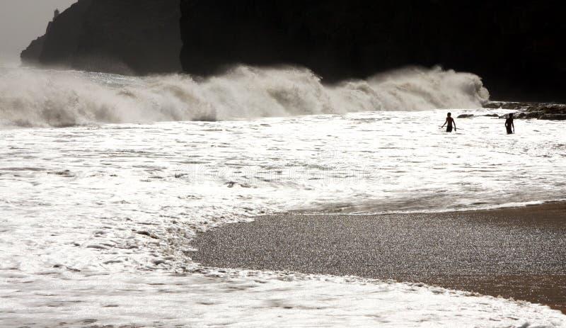 Falaise et nageurs dans les vagues photographie stock