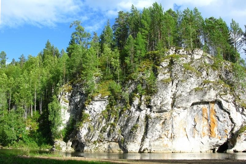 Falaise raide au-dessus de la rivière avec la forêt sur le dessus Jour ensoleillé lumineux, écoulement d'eau calme photographie stock