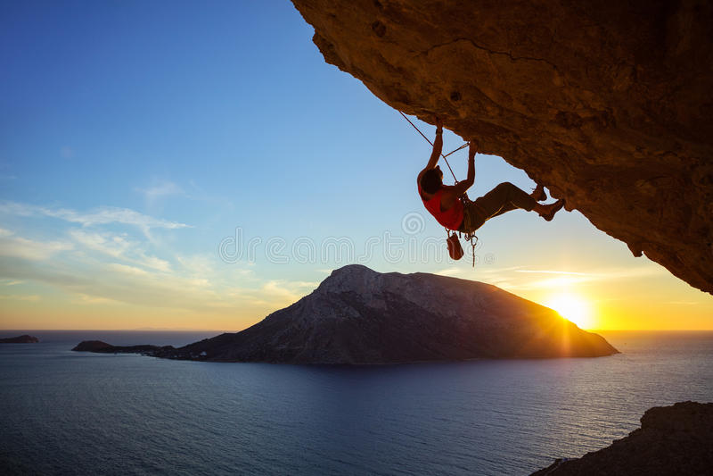 Falaise surplombante s'élevante de jeune homme au coucher du soleil photo libre de droits