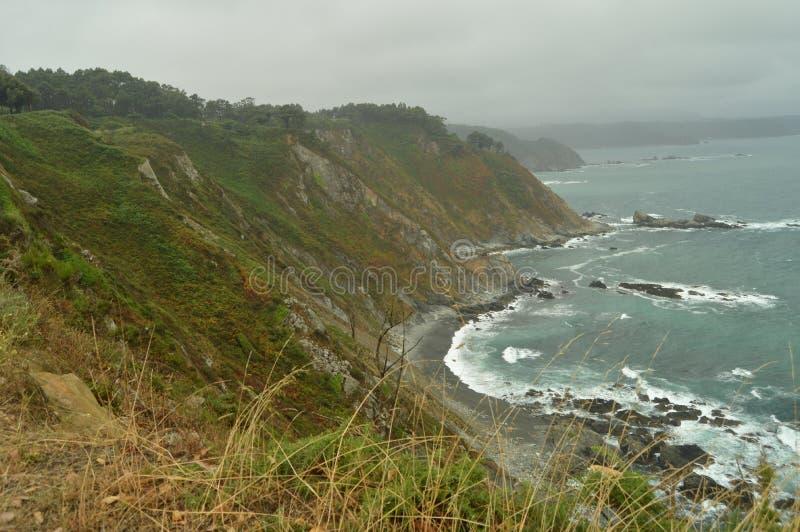 Falaises vertes avec des vagues de mer se cassant contre leurs roches à la plage de Las Llanas un jour pluvieux 29 juillet 2015 P photos stock