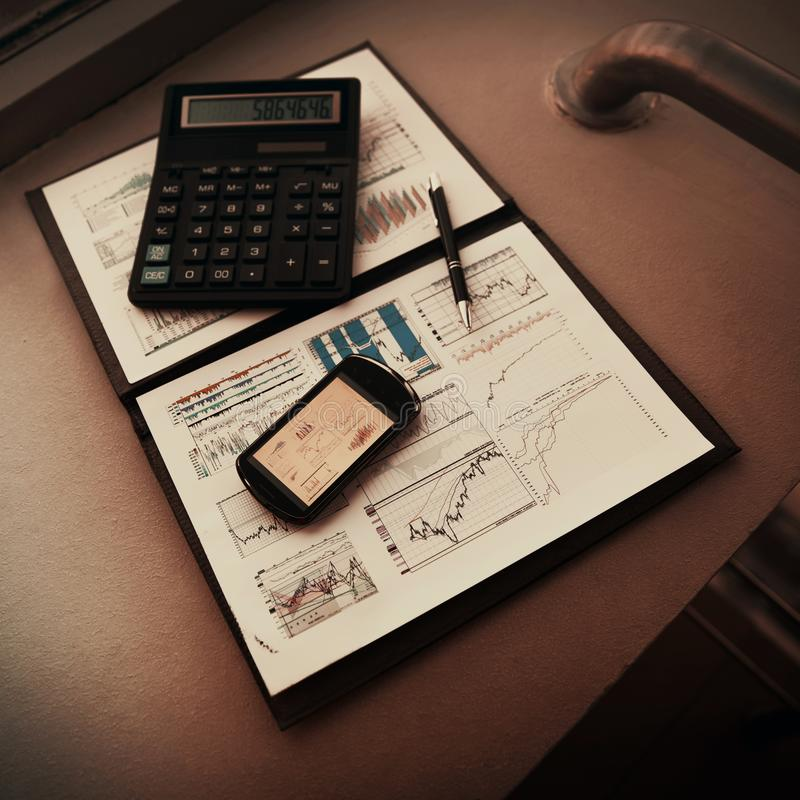 Falcówka z mapami pieniężna analiza Diagramy w telefonu ` s ekranie, następnie będą kalkulatorem i piórem zdjęcia royalty free