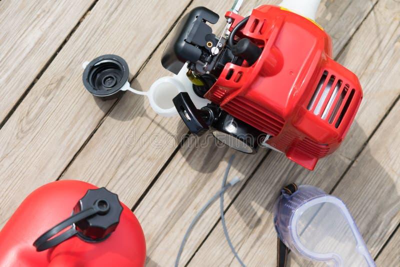 Falciatrice da giardino e scatola metallica rossa con la bugia della benzina su un fondo di legno fotografie stock libere da diritti